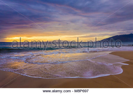 Sunset reflected in a gentle Pacific surf on Kamaole Beach Park 11 in Kihei on the island of Maui in the state of - Stock Photo