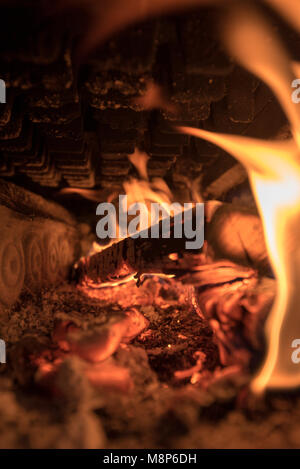 glow and fire inside an old cast iron stove - Stock Photo