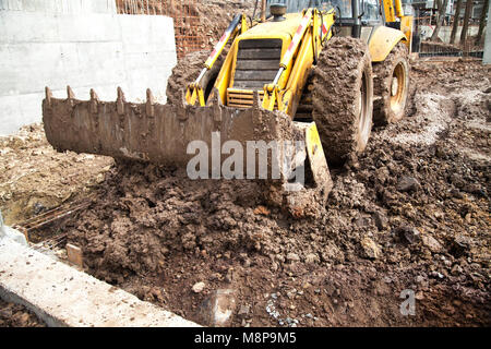 The tractor is leveling the area for construction. Dirt and wet earth with clay on the site. Building a house of - Stock Photo