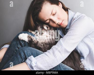 Stylish woman gently hugging kitten - Stock Photo