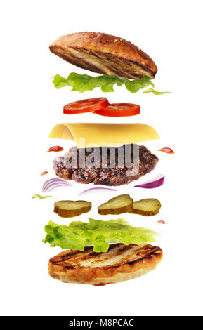 Delicious hamburger with flying ingredients isolated on white background. Freshly brewed burger closeup - Stock Photo