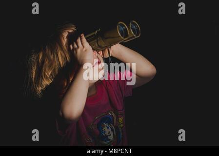 A young toddler girl looking through binoculars. - Stock Photo