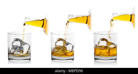 The process of pouring whiskey from bottle into glass - Stock Photo
