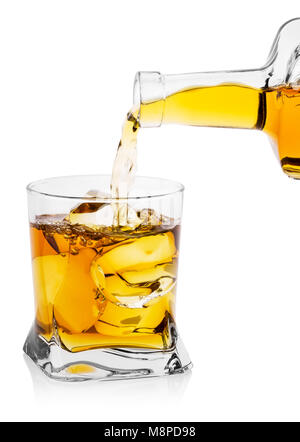 Whiskey pouring from bottle into transparent glass with ice - Stock Photo