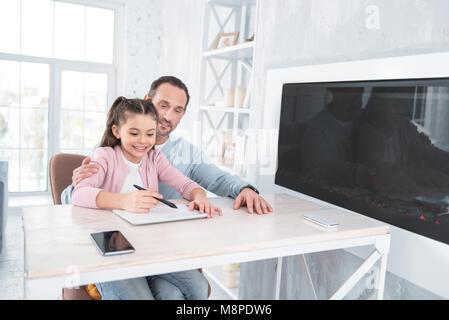 Nice positive girl doing her home task - Stock Photo