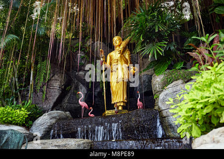 Golden Buddha statue in the tropical garden with waterfall in Wat Saket Golden Mountain Temple in Bangkok - Stock Photo