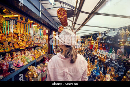 Tourist woman in hat and pink shirt at market with souvenirs in Bangkok, Thailand - Stock Photo