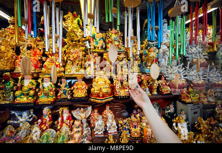 Hand of Tourist holding traditional bells at market with souvenirs in Bangkok, Thailand - Stock Photo