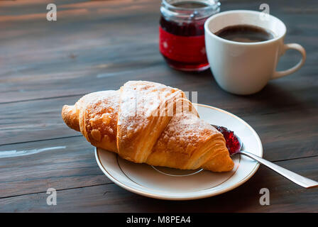 Breakfast with croissants, cup of black coffee and fruit - Stock Photo
