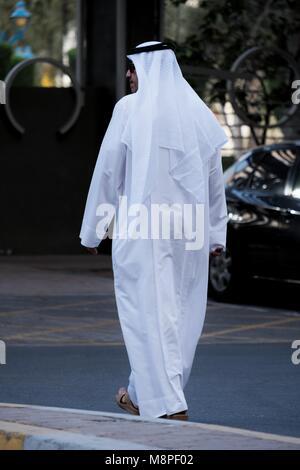 A local Emirati man in local Arab traditional dress walking near Hamdan Street Abu Dhbi - Stock Photo