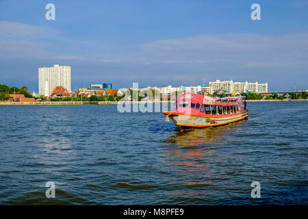 A local ferry boat is crossing the Chao Phraya River - Stock Photo