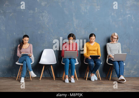 Nice young women using their devices - Stock Photo