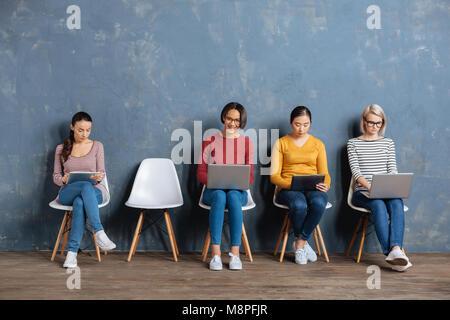 Cheerful positive women using modern technology - Stock Photo
