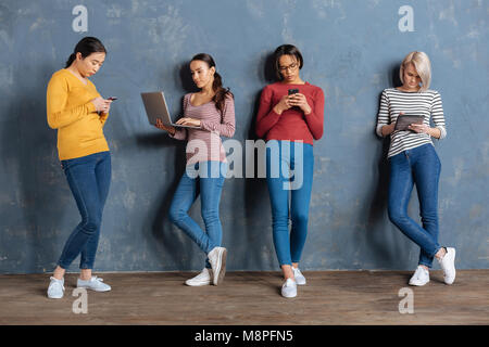 Serious young women leaning to the wall - Stock Photo
