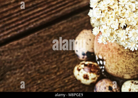 Quail eggs and dried flowers in little vase on old wooden table, top view. Easter vintage style  (selective focus). - Stock Photo