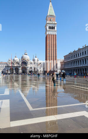 Reflection of the Campanile and Saint Marks Basilica in Acqua Alta, Piazza San Marco, Venice, Italy. The water was - Stock Photo
