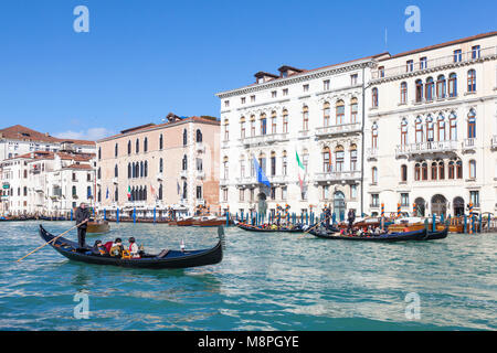 Tourists on  gondolas in the Grand Canal, San Marco, Venice, Veneto, Italy passing Palazzo Flangini Fini and Palazzo - Stock Photo