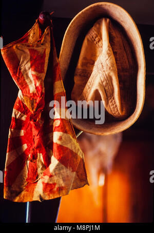 A World War Two US Navy sailor hat and a Japanese flag hang side by side on a WWII veterans wall - Stock Photo