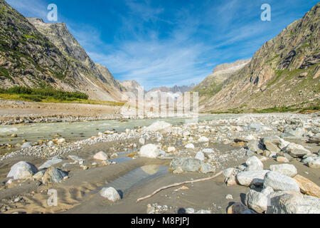 Lonely, glacial valley at the base of a glacier in the Swiss Alps. Glacier-fed stream, rocks and boulders dot the - Stock Photo