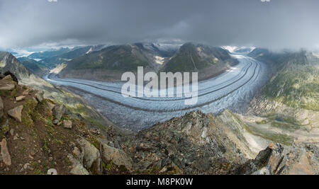 Panoramic view of Aletsch glacier, longest glacier in Europe. Curving glacier tongue, mountains, rocks and boulders - Stock Photo
