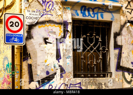 Graffiti mixes with flaking plaster and concrete on a delapidated building on a residential street in the north - Stock Photo