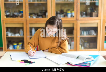 Young female college student in chemistry class, writing notes. Focused student in classroom. Authentic Education - Stock Photo