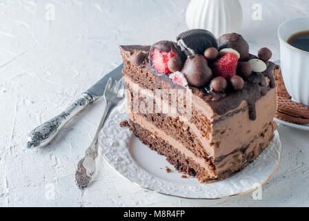 Piece of chocolate cake on white plate, cup of black coffee, jug and chocolate cookies  on white background. Top - Stock Photo