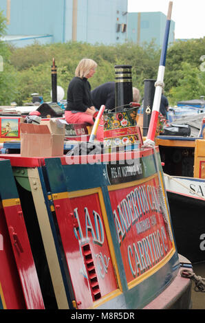 A lady sits on the cabin roof of a preserved canal boat moored amongst other colourful ones outside the Lion Salt - Stock Photo