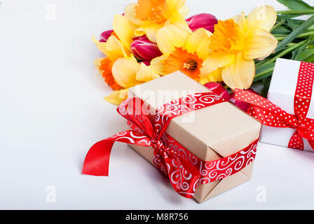 Top view  bouquet of  daffodils and gift box with red ribbon  on the black background.  flowers background concept - Stock Photo