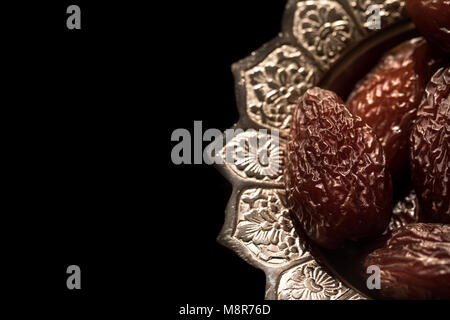 Close-up portrait of dates which are a traditional food to break fast during the holy month of ramadan on a silver - Stock Photo