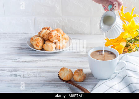 Breakfast, a cup of coffee and eclairs, flowers on a white background - Stock Photo