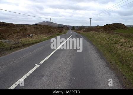 rural road empty to the horizon on the mizen peninsular, west cork, ireland - Stock Photo