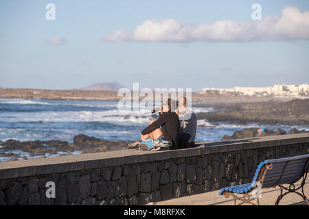 Young couple drinking while contemplating the sea in La Santa, Lanzarote, Canary Islands, Spain - Stock Photo