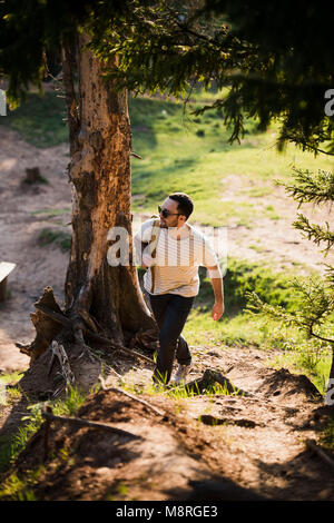 Happy bearded man traveler with backpack walking in forest. Tourism, travel, adventure, hike concept - smiling young - Stock Photo