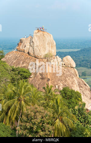 Aradhana Gala rock opposite Mihintale which pilgrims and tourists climb to pray or look at the view on a sunny day - Stock Photo