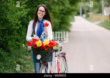 Portrait of cheerful young woman with bicycle holding tulip on road - Stock Photo
