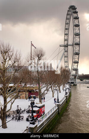 london eye on queens walk' in the snow. southbank ot the river Thames - Stock Photo