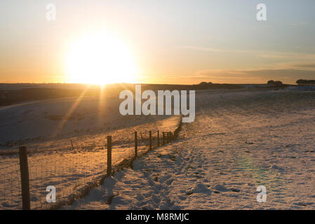 Fence on snow covered field against sky during sunset - Stock Photo
