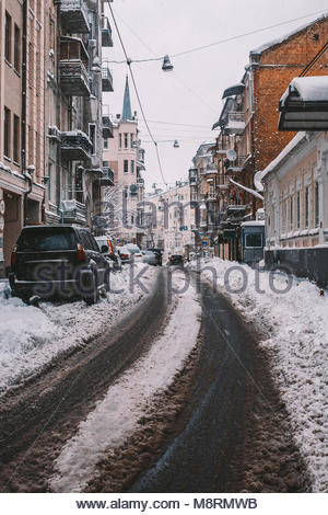 Cars parked on snow covered road amidst buildings in city - Stock Photo