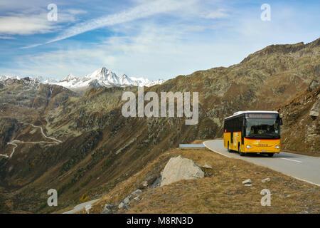FURKAPASS, SWITZERLAND - OCTOBER 2017 - Typical yellow Postbus in Switzerland on high altitude Furka pass road. - Stock Photo