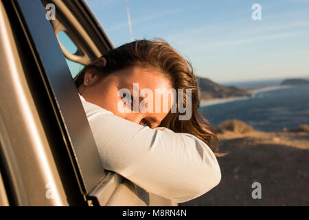 Portrait of woman looking through car window at beach against sky during sunset - Stock Photo