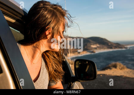 Woman looking through car window at beach against sky during sunset - Stock Photo