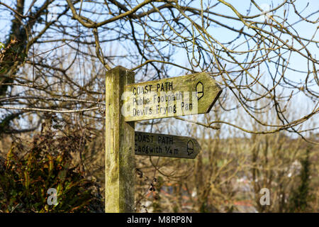 A wooden signpost saying 'Coast path', 'Public Footpath', 'Cadgwith  1/4 m' and 'Devil's Frying Pan' Lizard Peninsula, - Stock Photo