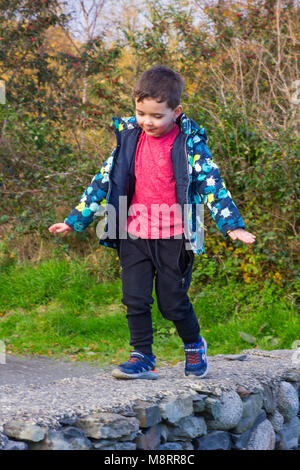 An infant boy walking and balancing on top of a stone wall in Castlewellan in Northern Ireland growing up - Stock Photo