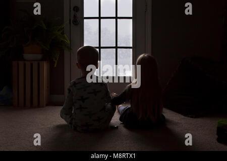 Rear view of siblings looking through window while sitting on floor in darkroom - Stock Photo