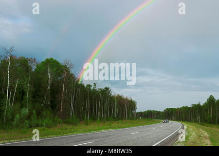 Rainbow after rain over highway in the summer - Stock Photo