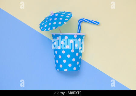 Tropical drink minimal creative summer flat lay concept made of paper polka design cup, paper umbrella and drinking - Stock Photo