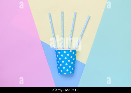 Paper party cup polka design with drinking straws on colorful pastel background flat lay minimal creative concept. - Stock Photo