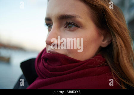 Close-up of thoughtful woman wearing scarf outdoors - Stock Photo