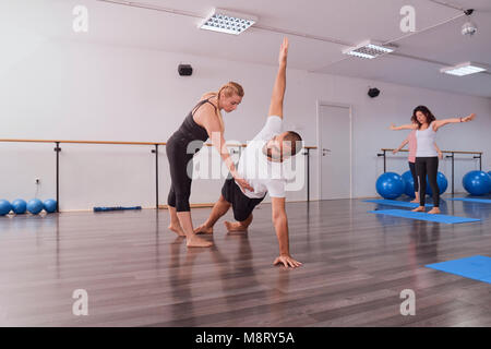 Yoga instructor teaching posture to man exercising in pilates class - Stock Photo
